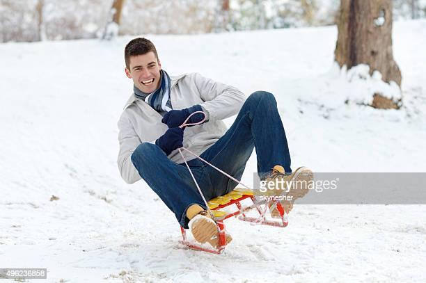 Glücklicher Mann sledging Ski auf einem Schnee.