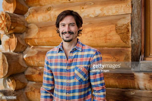 happy man standing against log cabin - mid adult men stock-fotos und bilder