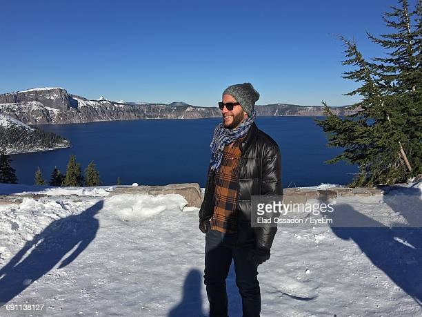Happy Man Standing On Snow Covered Field Against Lake