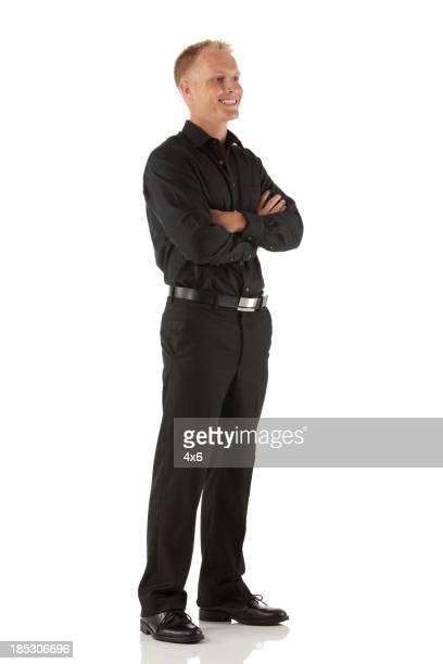 Glücklicher Mann stehend mit Arme verschränkt