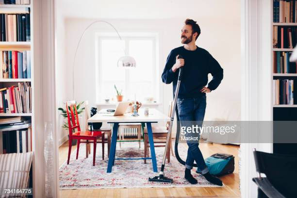 happy man standing with vacuum cleaner in dining room at home - ein mann allein stock-fotos und bilder