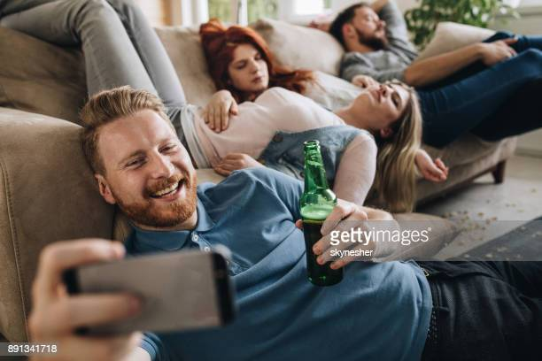 happy man taking a selfie of him and his wasted friends at home. - hangover after party stock pictures, royalty-free photos & images