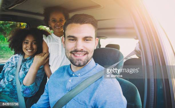 happy man taking family for road trip in car - family driving stock photos and pictures