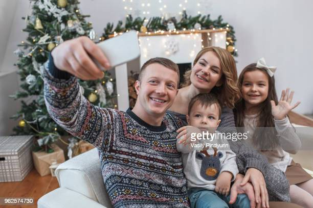 Happy man taking selfie with family on sofa at home during Christmas