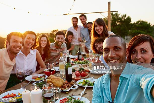 Happy man taking selfie with friends