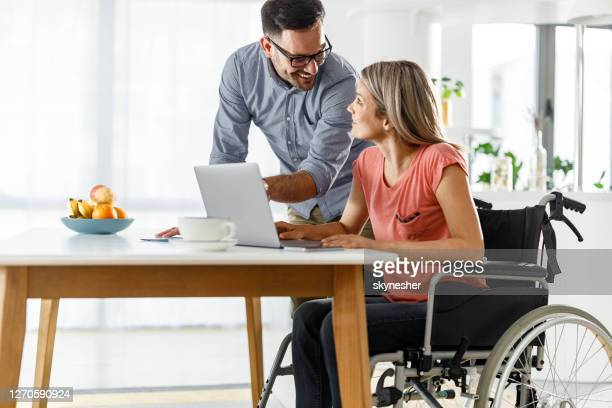 happy man talking to his girlfriend in wheelchair while using laptop at home. - persons with disabilities stock pictures, royalty-free photos & images