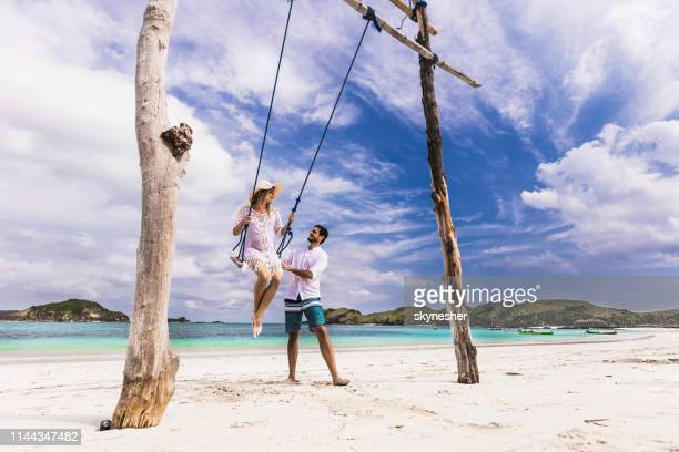 un hombre feliz hablando con su esposa en un columpio en la playa. - lombok fotografías e imágenes de stock
