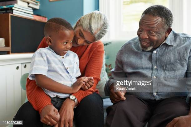 happy man talking with cute boy standing at home - disruptaging stock pictures, royalty-free photos & images