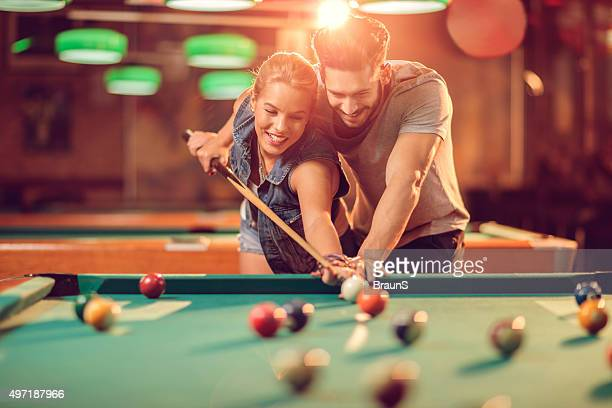 Happy man teaching his girlfriend how to play snooker.