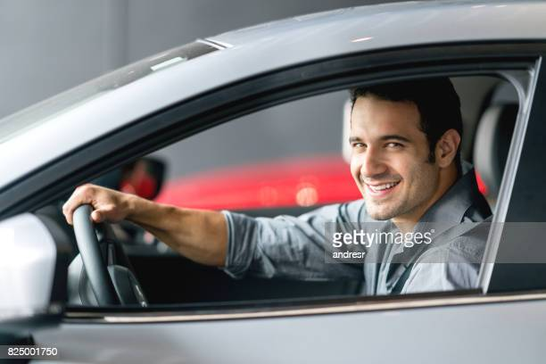 happy man test driving a car and looking at the camera smiling - test drive stock pictures, royalty-free photos & images