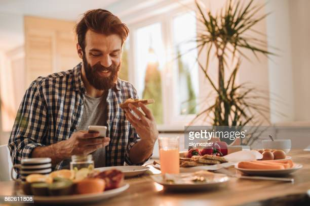 Happy man text messaging on cell phone during breakfast time.