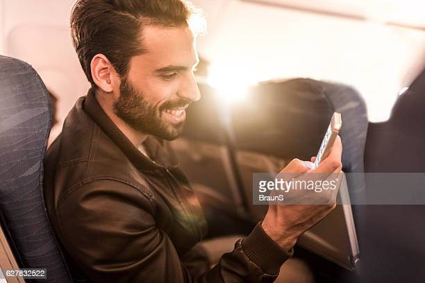 Happy man text messaging on cell phone in the airplane.