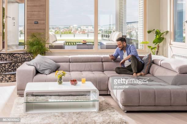 homme heureux sms sur téléphone portable tout en vous relaxant dans le salon. - un seul homme photos et images de collection