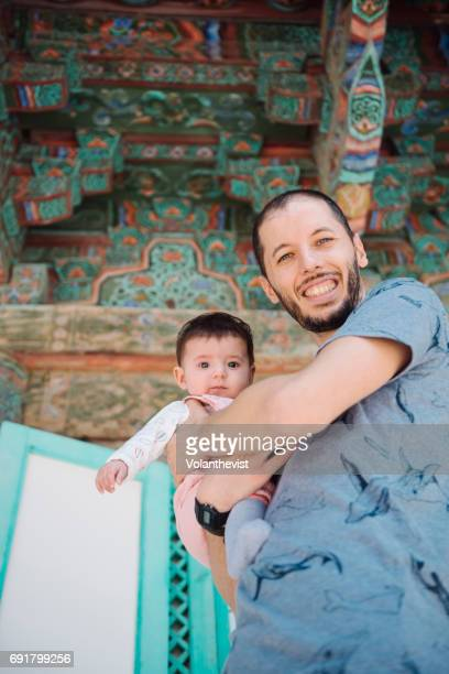 Happy man traveling with a baby girl in a temple in South Korea