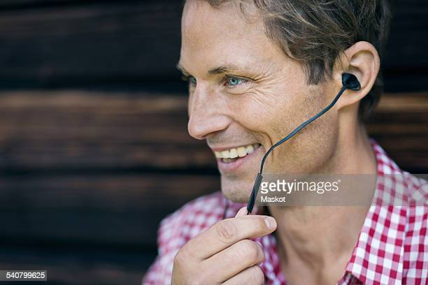 Happy man using hands-free device outside log cabin