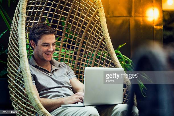 happy man using laptop in hanging chair - 40 49 years stock pictures, royalty-free photos & images