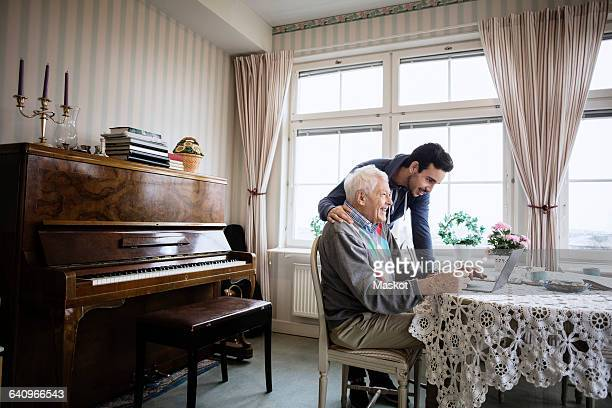 happy man using laptop with caretaker in nursing home - focus on background stock pictures, royalty-free photos & images