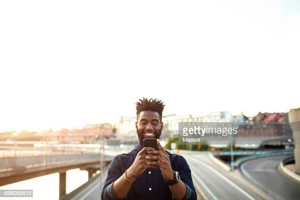 Happy man using mobile phone over city street against sky