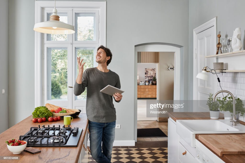 Happy man using tablet in kitchen looking at ceiling lamp : Stock Photo