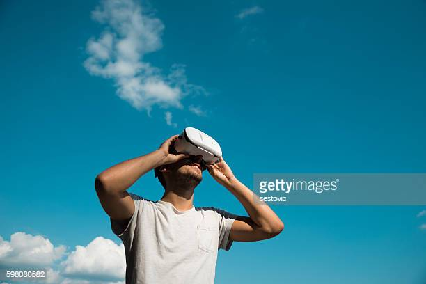 Happy man using VR glasses outside