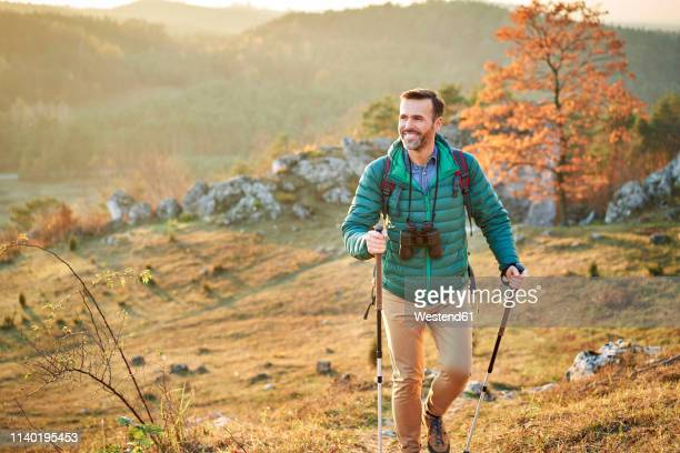 happy man walking on trail on a hiking trip in the mountains - hiking pole stock pictures, royalty-free photos & images