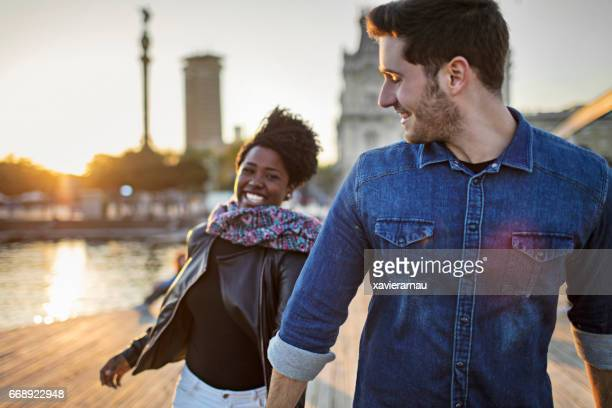 happy man walking with woman on boardwalk in city - boardwalk stock pictures, royalty-free photos & images