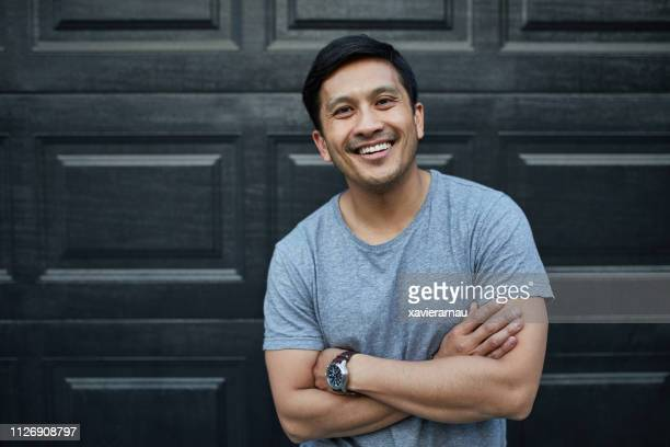 happy man with arms crossed against wall at yard - 35 39 years stock pictures, royalty-free photos & images