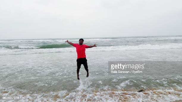 Happy Man With Arms Outstretched Jumping Over Sea Against Clear Sky