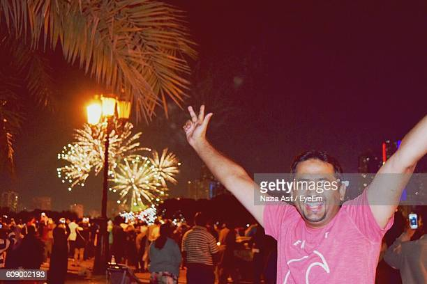 Happy Man With Arms Raised Standing Against Firework Display At Night