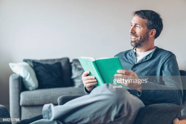 Happy man with book at home