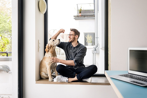 Happy man with dog sitting at the window - gettyimageskorea