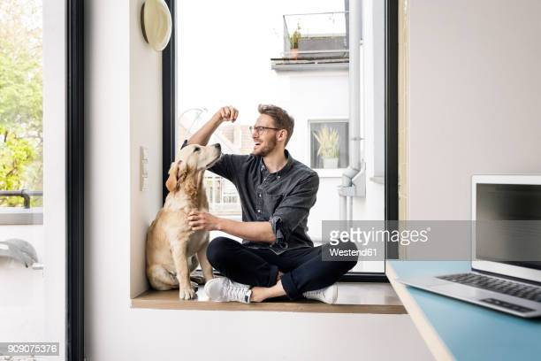 happy man with dog sitting at the window - pet owner stock pictures, royalty-free photos & images