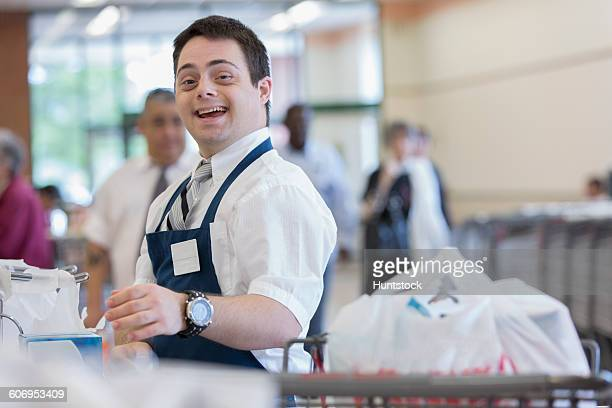 Happy man with Down Syndrome working at a grocery store