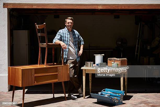 Happy man with furniture outside house