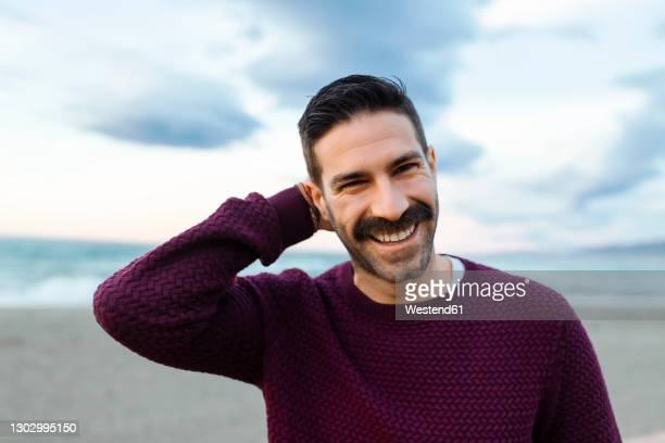 happy man with hands behind head at beach during sunrise - maroon stock pictures, royalty-free photos & images