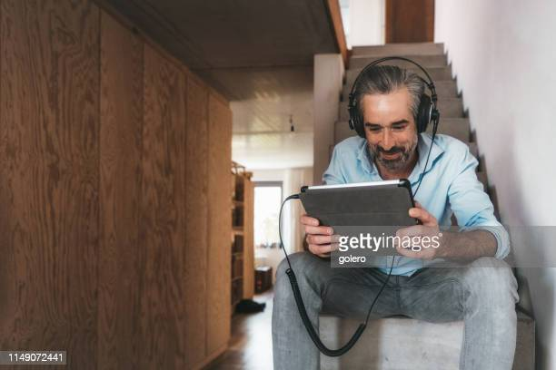happy man with headphones and tablet sitting on concrete stairs - live streaming stock pictures, royalty-free photos & images