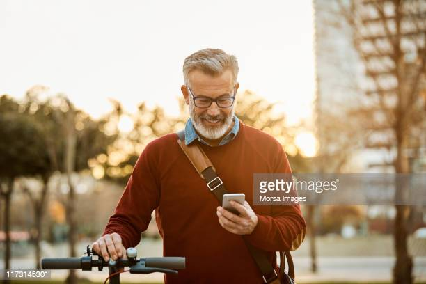 happy man with mobile phone and bicycle in city - mature men stock pictures, royalty-free photos & images
