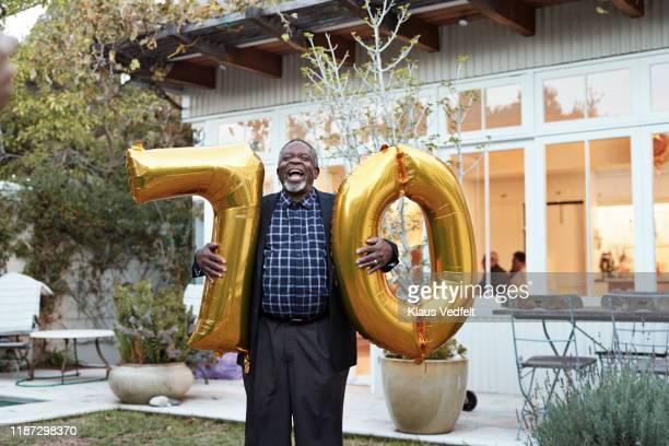 happy man with number 70 helium balloons in backyard - 70 79 jaar stockfoto's en -beelden