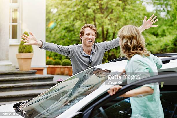 Happy man with outstretched arms looking at woman at car