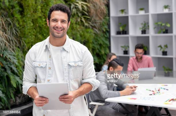 Happy man working at a creative office using a tablet computer