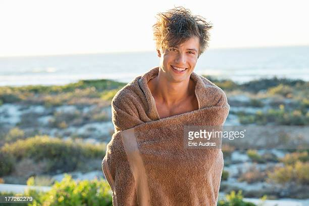 Happy man wrapped in a towel standing on the beach