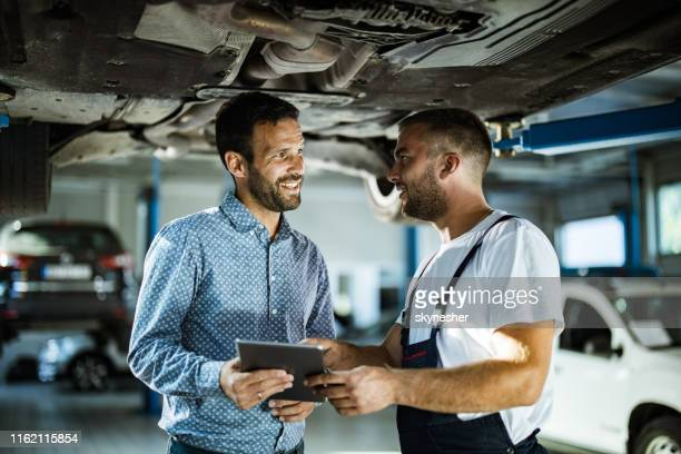 happy manager and auto mechanic talking while using touchpad in a workshop. - chassis stock pictures, royalty-free photos & images