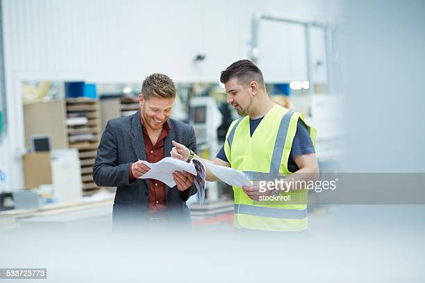 Happy manager and foreman checking reports