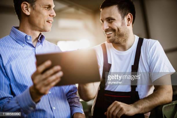 glücklicher manager und arbeiter im gespräch, während er touchpad in einer werkstatt verwendet. - handwerker stock-fotos und bilder