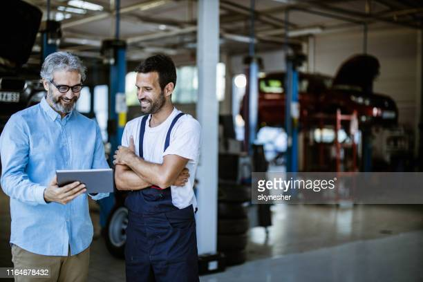 happy manager and mechanic using digital tablet in auto repair shop. - auto repair shop stock pictures, royalty-free photos & images