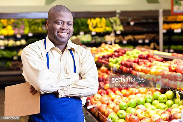 Happy manager at a grocery store produce area