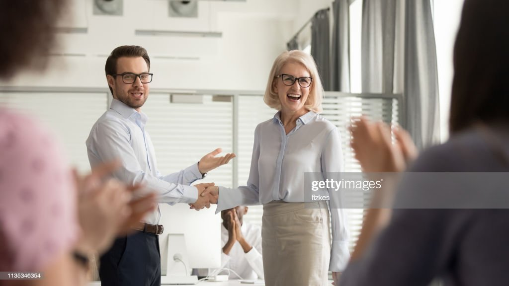 Happy manager boss praising old employee get team appreciation : Stock Photo