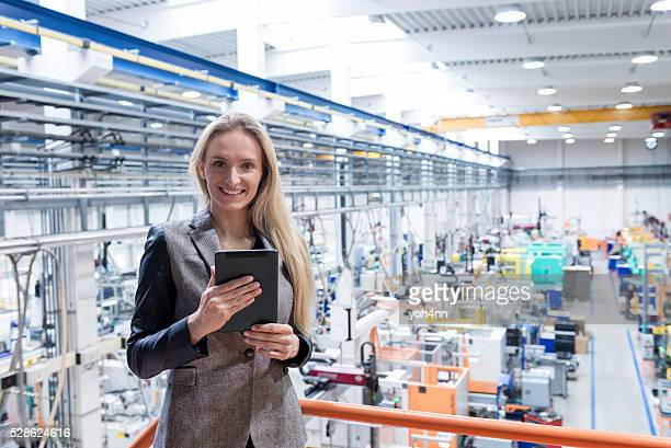 Happy manager with tablet on top of large factory