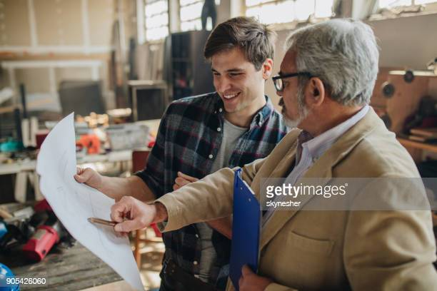 Happy manual worker and senior inspector analyzing blueprints in repair shop.