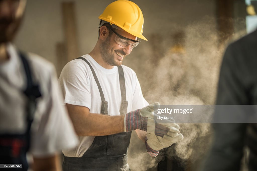 Happy manual worker cleaning his gloves from sawdust at construction site. : Stock Photo